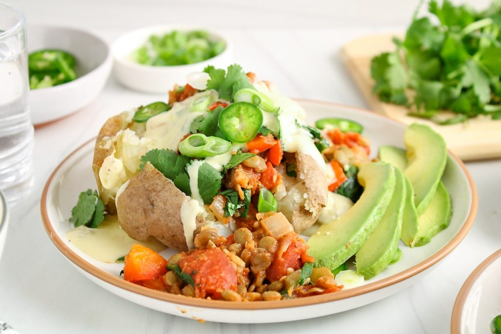 Showing is a Mexican baked potatoes stuffed with a lentil chili stew, a vegan white queso and fresh cilantro, jalapeno and green onion. There are a few slices of avocado on the side of the avocado. Also on the table, there are a few bowls with more of the vegan white queso, half of an avocado, sliced jalapeno, cilantro and green onion.