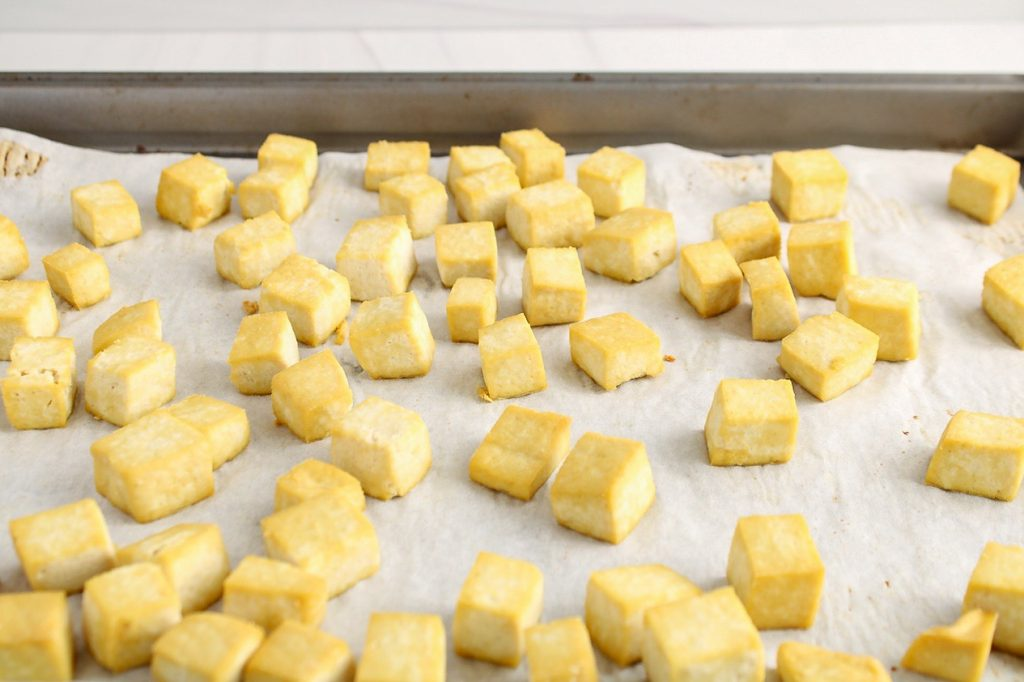 There are cubes of tofu cooked on a baking sheet covered with parchment paper.