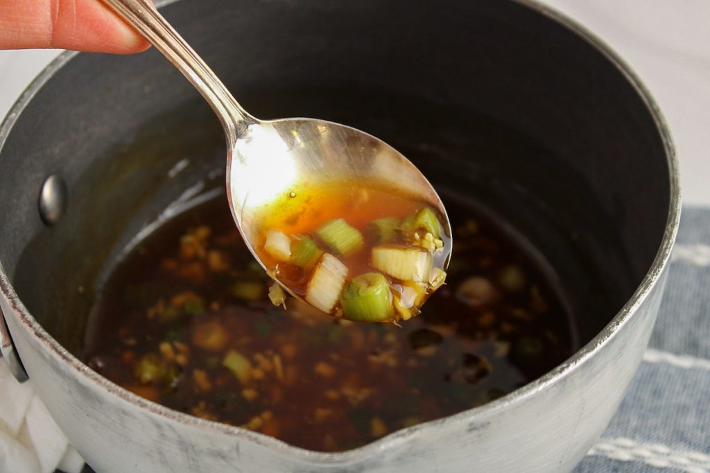 There is a spoon above a small sauce pan showing the texture of the sauce in the pot.