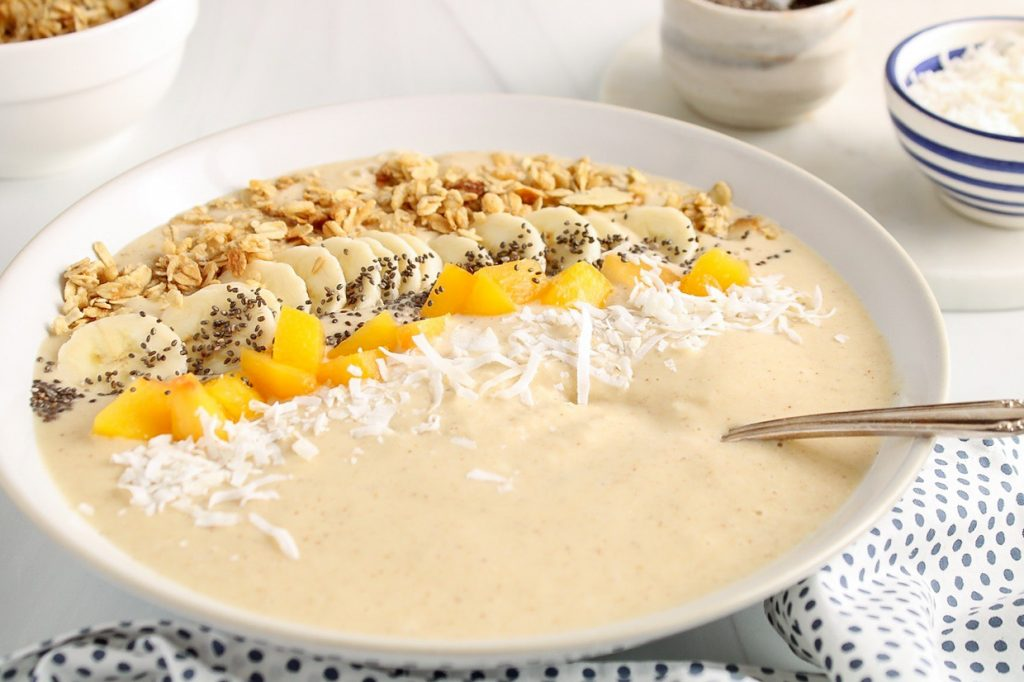 Showing is a peach oatmeal smoothie bowl topped with granola, peaches, coconut flakes, bananas and chia seeds. There are a few bowls in the background with more chia seeds, coconut and granola.