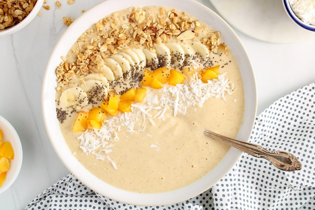 Showing is a peach oatmeal smoothie bowl topped with granola, peaches, coconut flakes, bananas and chia seeds. There are a few bowls on the side with more chia seeds, coconut and granola. There is a spoon in the bowl and a blue and white polkadots hand towel on the side.