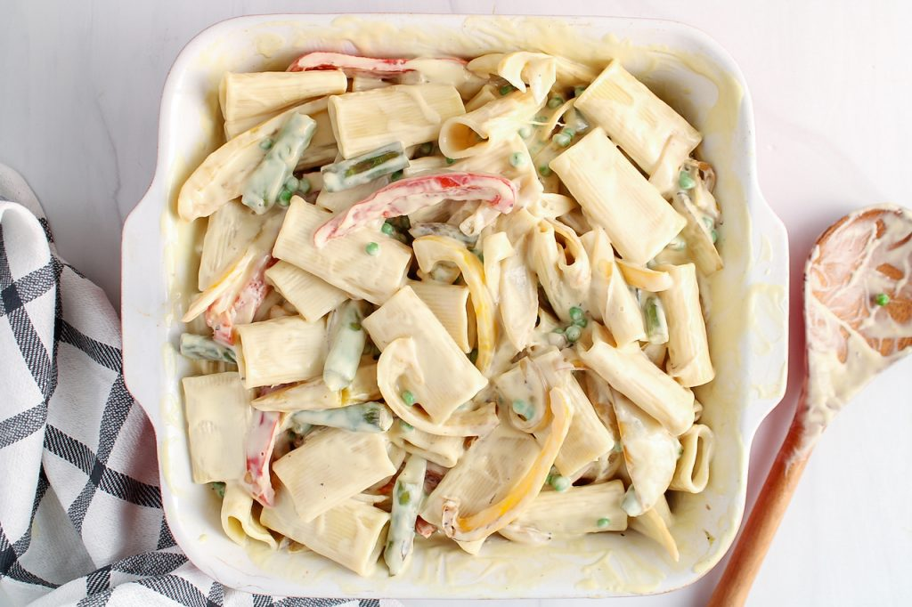 There is a oven baking dish containing noodles with vegetable and a white creamy sauce. There is a wooden spoon on the side as well as a black and white hand towel.