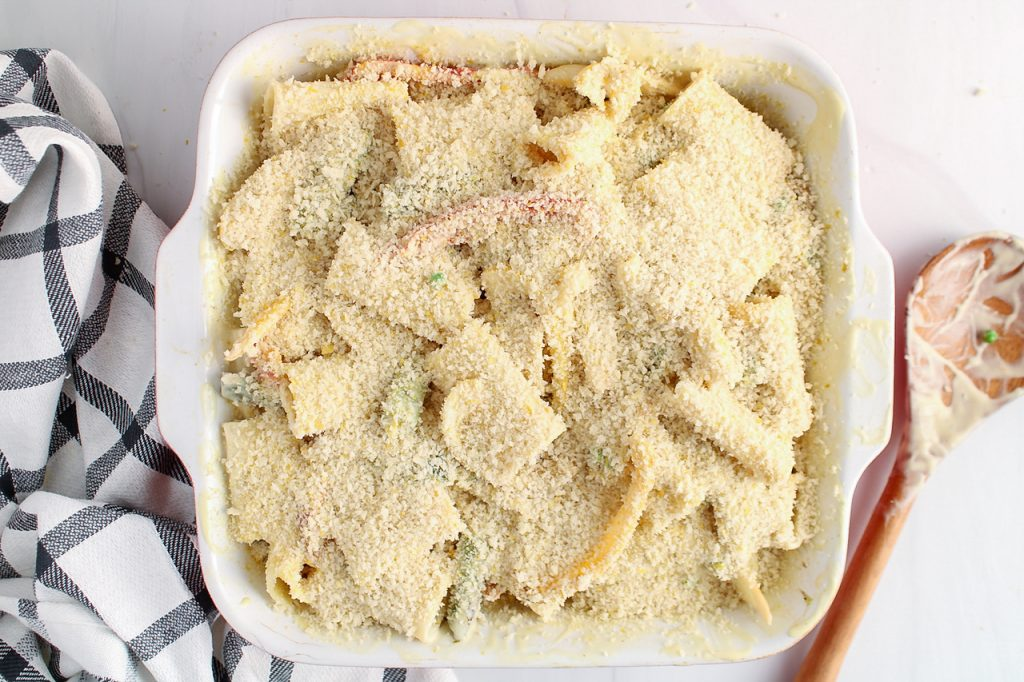 There is a oven baking dish containing noodles with vegetable and a white creamy sauce garnished with a panko mixture. There is a wooden spoon on the side as well as a black and white hand towel.