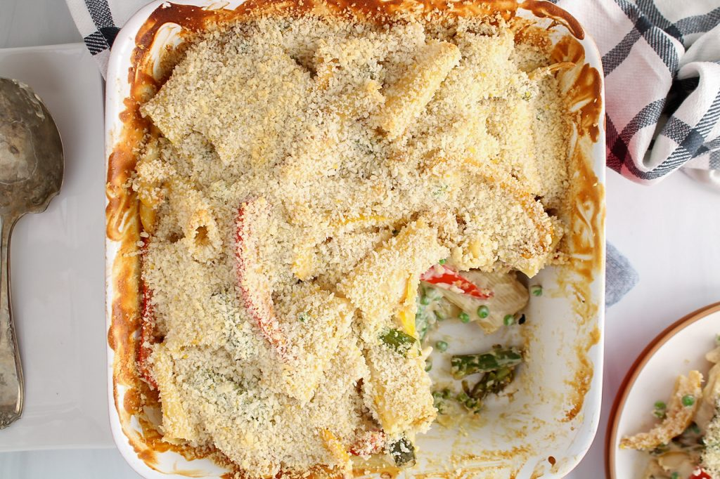 There is a oven baking dish containing noodles with vegetable and a white creamy sauce garnished with a panko mixture. There is a silver spoon on the side as well as a black and white hand towel. There is a portion of the pasta bake gone.