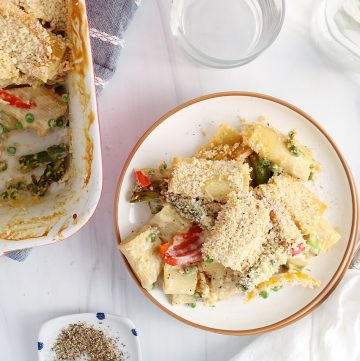 There is a portion of a vegan garlic pasta bake on a plate with a baking dish containing more of the pasta on the side. There are 2 forks, 2 glass and a pitcher of water on the side as well as a small plate with ground black pepper.