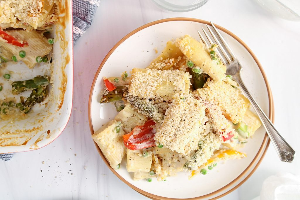 There is a portion of a vegan garlic pasta bake on a plate with a baking dish containing more of the pasta on the side. There is a fork on the plate as well.