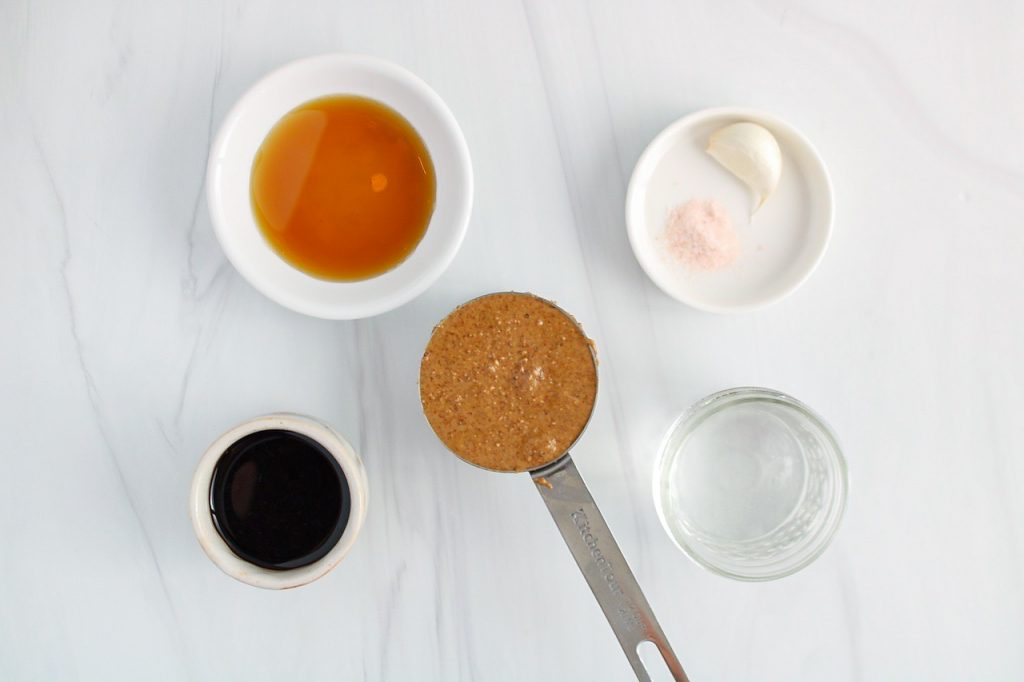 Showing are a few bowls containing nut butter, balsamic vinegar, a clove of garlic, salt, water and maple syrup.