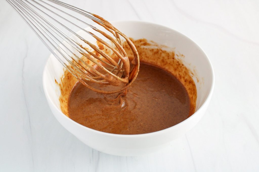 Close up on a large whisk dipping in a white bowl containing a creamy vinaigrette to show the texture of the sauce.