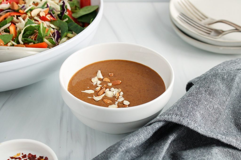 There is a white bowl containing a almond butter dressing topped with chopped almonds. There is a large bowl containing a coleslaw on the side as well as 2 forks, red pepper flakes, a dark grey hand towel and 2 plates.