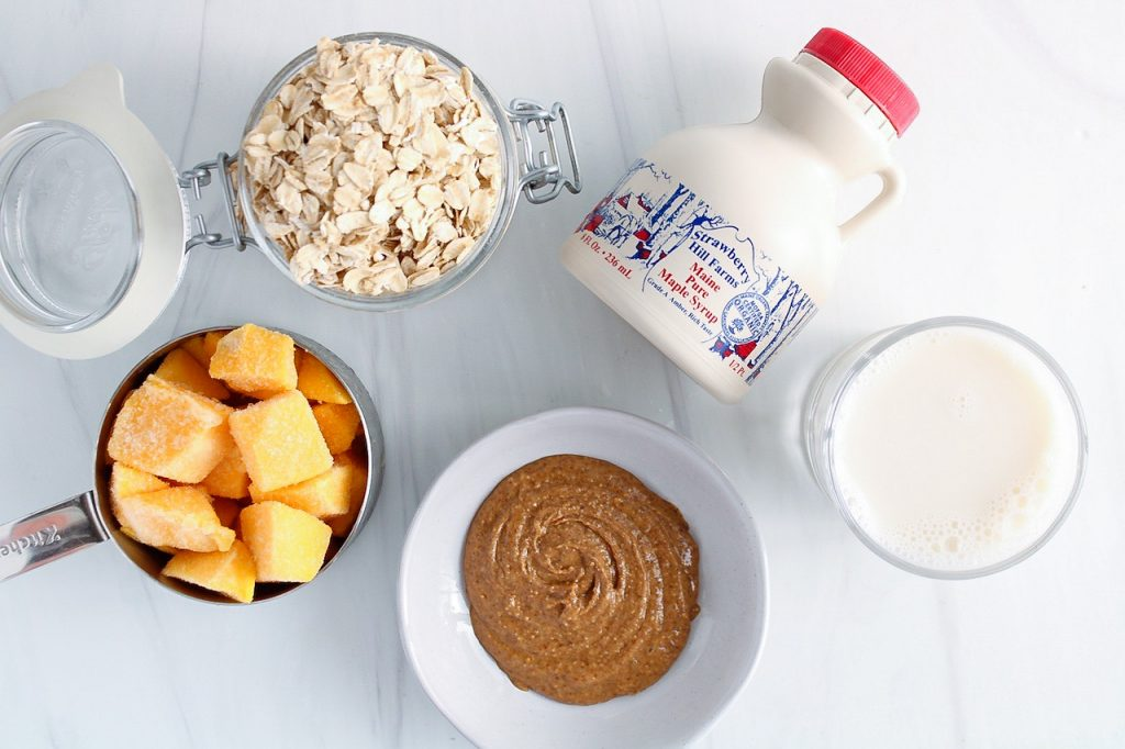 Ingredients to make this recipe: frozen mango, raw oats, maple syrup, vegan milk, almond butter.