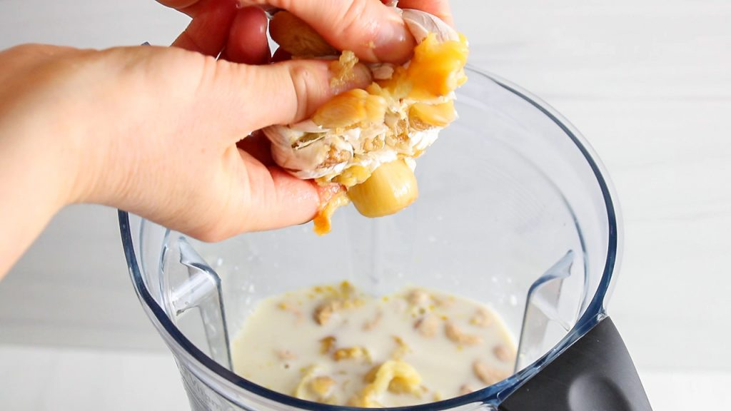 You can see hand holding a head of roasted garlic that is pressing at the base to add the garlic to a blender.