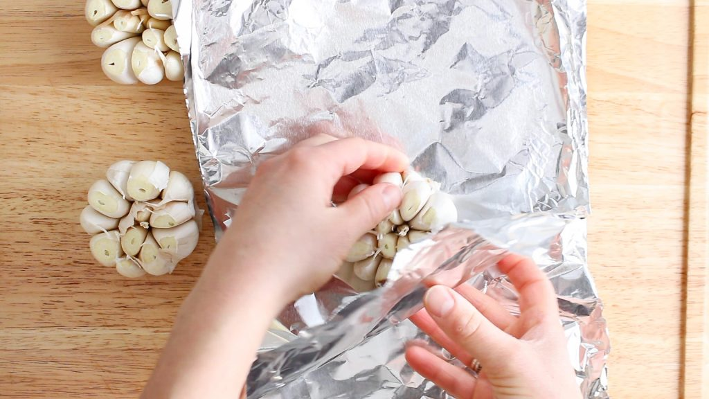 There are 2 hands wrapping a head of garlic in aluminium foil