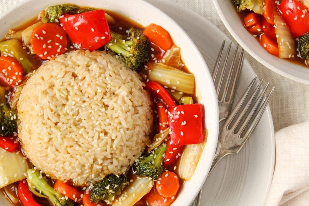 2 bowls are displayed and containing an healthy vegetable Stir-fry with broccoli, red pepper, carrot and onion. The stir-fry is topped with brown rice and there are 2 forks on the side of one of the bowl. Beside the bowls, there is a small bowl containing sesame seeds.