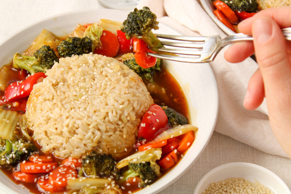 Close up on a bowl containing an healthy vegetable Stir-fry (with red pepper, carrots, broccoli and onions) that is topped with brown rice. Also, there is a fork being hold by a hand holding a piece of broccoli.