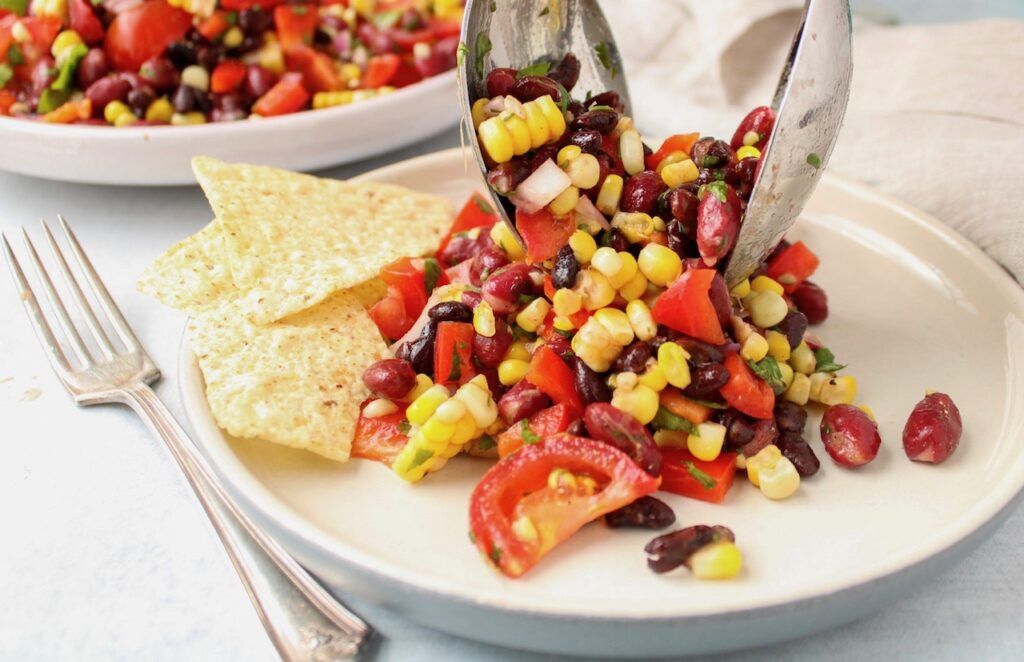 There is a healthy bean salad on a white plate with a few tortilla chips on the side. Also on the table beside the plate, there is a fork and you can see more of the bean salad in the background in a large plate. There are 2 large spoon also putting more of the salad on the small plate.