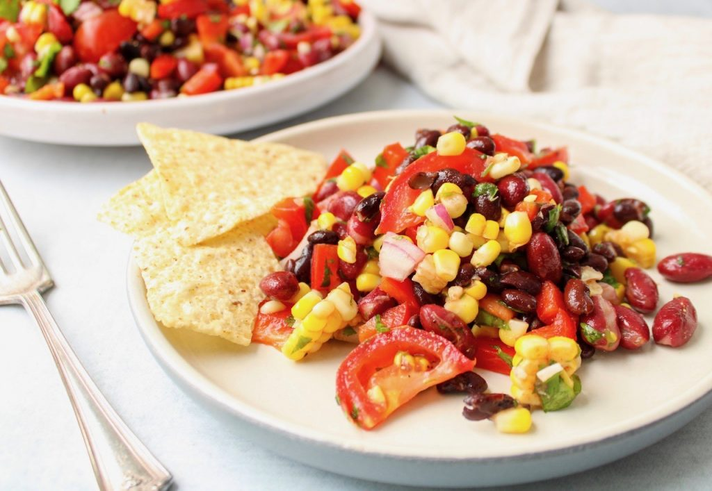 There is a healthy bean salad on a white plate with a few tortilla chips on the side. Also on the table beside the plate, there is a fork and you can see more of the bean salad in the background in a large plate.