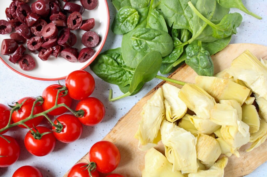 Displayed are a few ingredients to make a greek style roll: tomatoes, kalamata olives, artichoke and spinach
