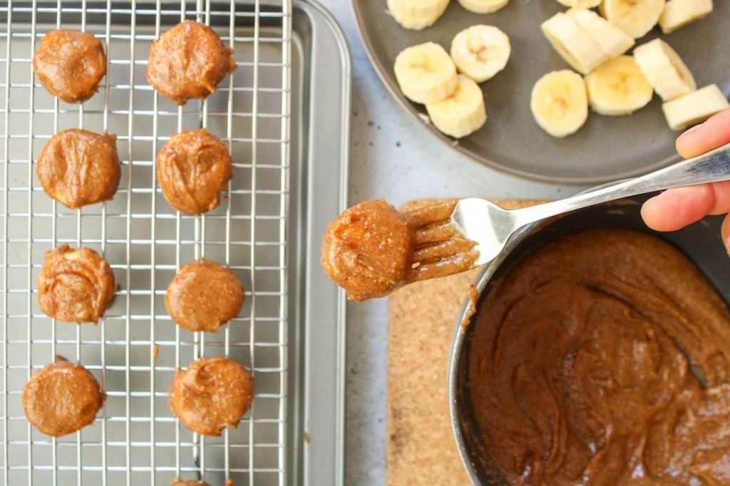You can see a cooling rack with a few pieces of banana that were just rolled in an almond butter mixture. You can also see a plate with sliced bananas and a small pot with an almond butter mixture. There is a close up on a fork holding a pieces of banana that was just rolled in the nut butter.