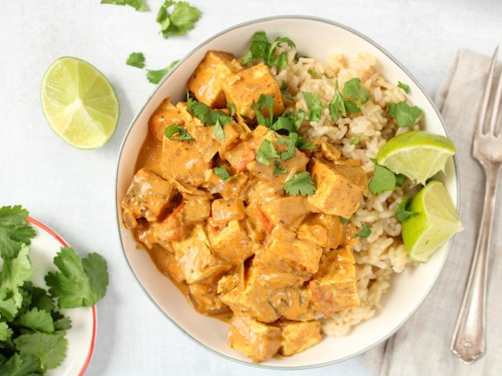 A bowl is filled with brown rice and vegan tofu tikka masala (a pink-red creamy sauce), with a few pieces of chopped cilantro on top and sliced lime on the side of the bowl. On table beside, there is a fork, a lime wedge and more cilantro on a white plate.