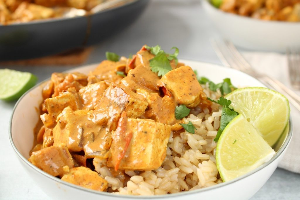 A bowl is filled with brown rice and vegan tofu tikka masala (a pink-red creamy sauce), with a few pieces of chopped cilantro on top and sliced lime on the side of the bowl. On table beside there is a fork and a lime wedge . Also, in the background, you can see an other bowl of rice and masala and the pan containing the tikka masala sauce.