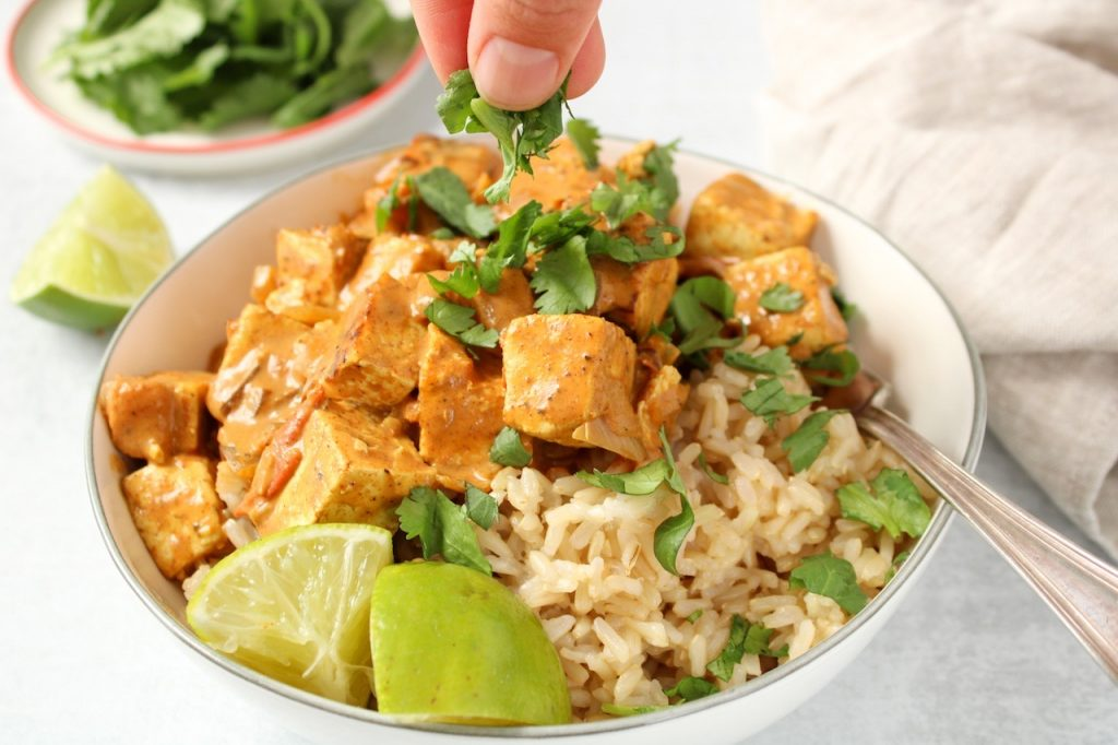 A bowl is filled with brown rice and vegan tofu tikka masala (a pink-red creamy sauce), with a few pieces of chopped cilantro on top and sliced lime on the side of the bowl. On table beside there is a lime wedge, a beige towel and more cilantro on a white plate. You can see the hand of someone sprinkling more chopped cilantro on top of the bowl.