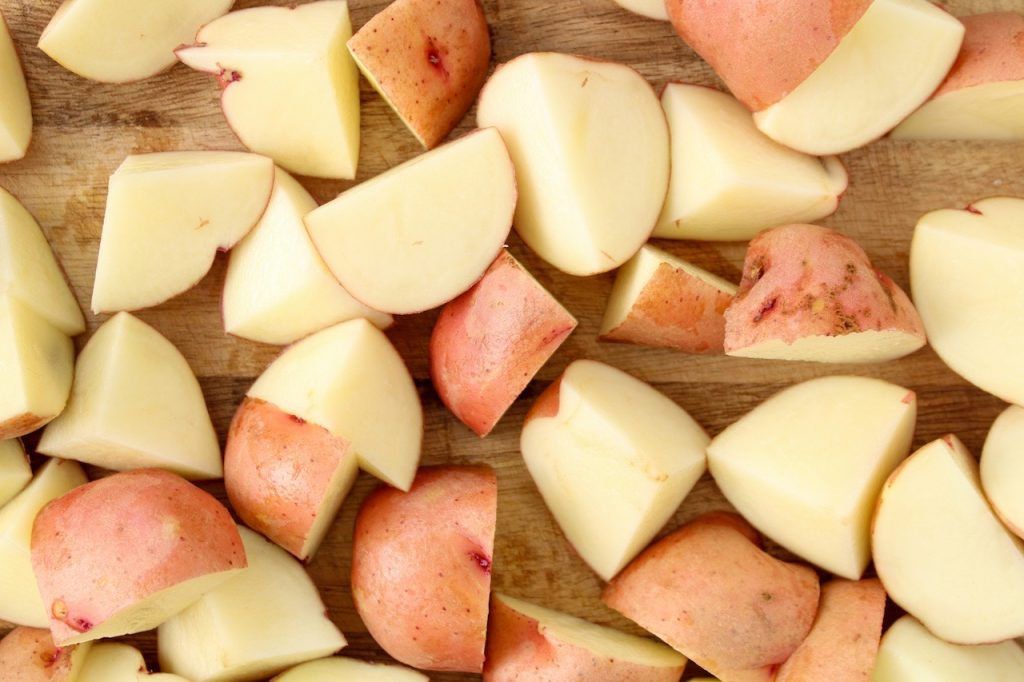 Chopped red potatoes spread on a cutting board