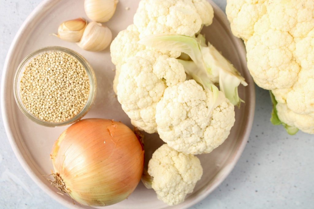 Displayed are the ingredients needed to make a creamy vegan cauliflower soup: cauliflower, white onion, 3 cloves of garlic and white quinoa in a small bowl. All the ingredients are displayed on a plate with head over shot.