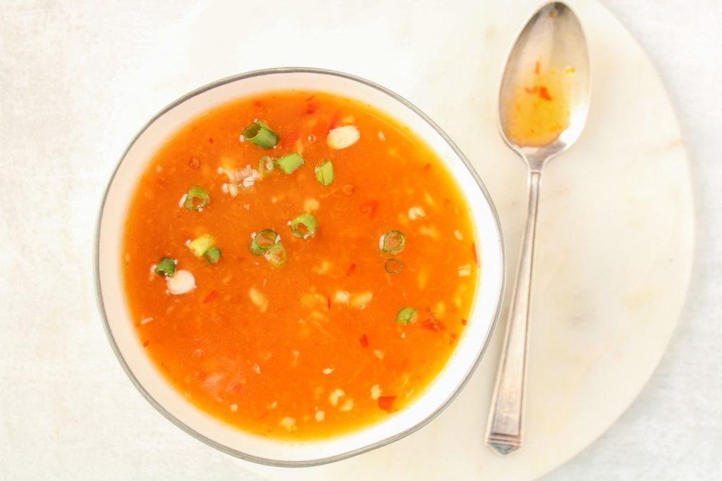 In a white bowl, you can see an orange sauce. The bowl is on a white plate. Also on the side, there is a small spoon covered in the sauce.