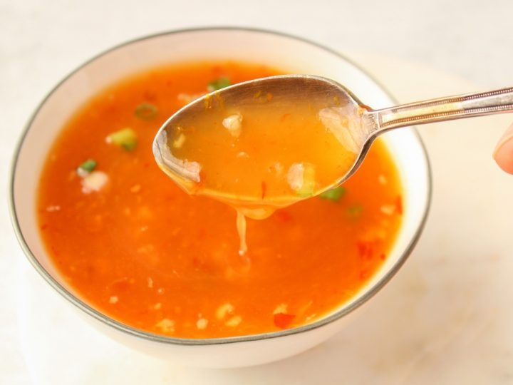 Close up on a spoon behind hold by a hand showing a sweet and spicy orange sauce falling from the spoon into a bowl containing g more of the sauce.