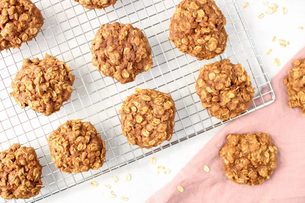A few cinnamon oatmeal cookies are distribute on a cooling rack to cool down. Also on the side, you can see a pink hand towel with 2 cookies on top and a few sprinkle of raw oats around.