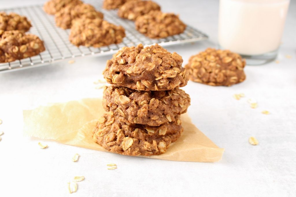 3 cinnamon oatmeal cookies are piled on top of each other on a pale blue table. In the background, you can see more cookies cooling down on a cooling rack and a glass of milk.