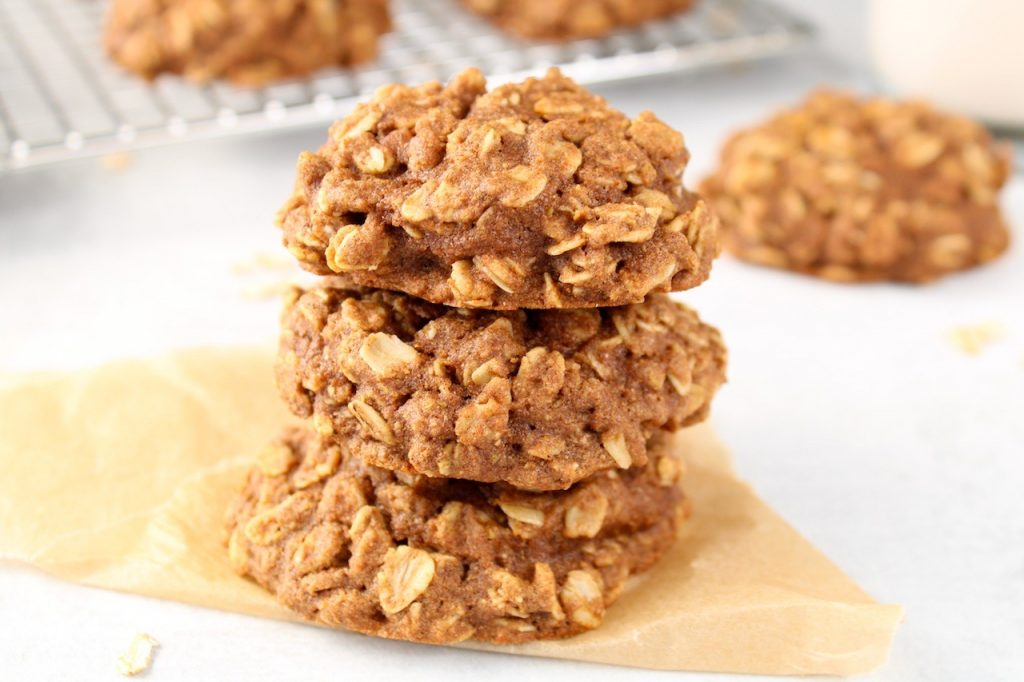 3 cookies are pile on top of each other on a pale blue table. In the background, you can see more cookies and a glass of milk.