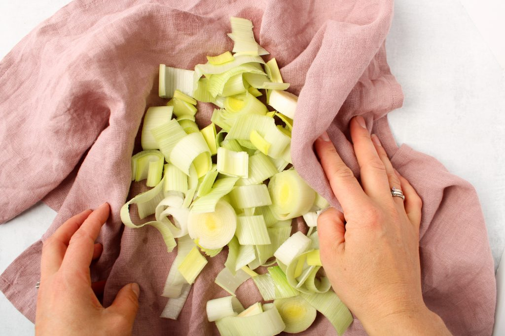 In a pink towel, there are pieces of leeks being dried up. You can see 2 hands rubbing the leeks with the towel.