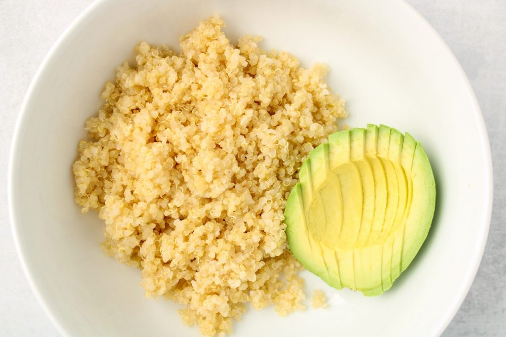 In the making of a savory breakfast quinoa bowl. In a white bowl, there is white quinoa and half of an avocado.