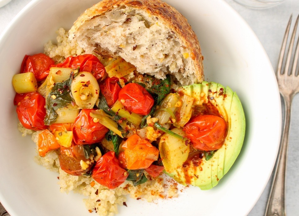 A savory breakfast quinoa bowl is displayed in a white bowl. You can see white quinoa topped with a leek and tomato compote. Also on the side, there are half of an avocado and a piece of bread. On the table beside the bowl, there is a fork.