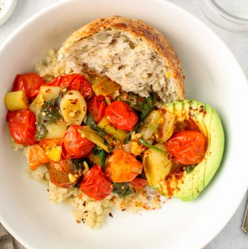 Showing is a savory breakfast quinoa bowl. At the bottom of the bowl, there is white quinoa topped with a leek and tomato compote. Also on the side, there are half of an avocado and a piece of bread. On the table beside the bowl, there is a fork, a glass of water and a small white bowl containing red pepper flakes.