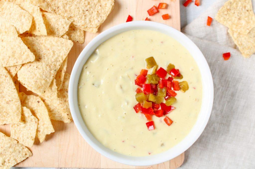 In a white bowl, there is a vegan white Queso topped with diced red pepper and green chiles. On the side, there are tortilla chips.