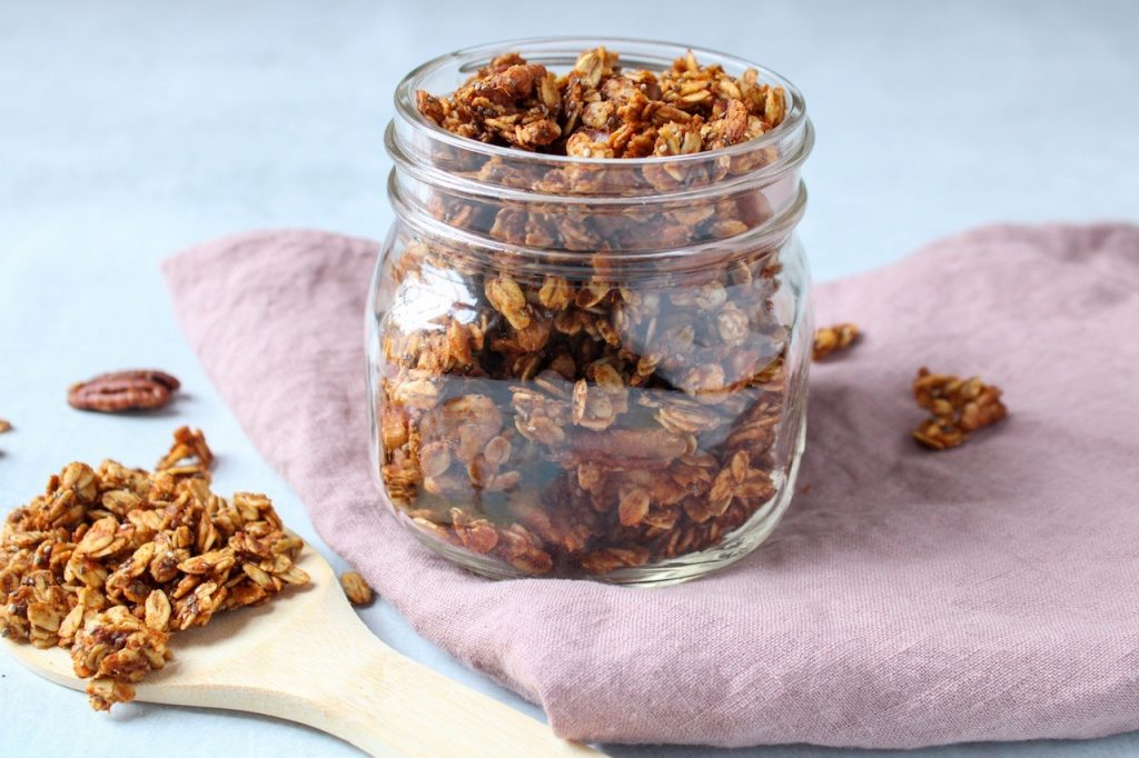 On a pink hand towel, there is a glass jar containing some sweet potato granola. On the side, there is a wooden spoon holding a little bit of the granola.