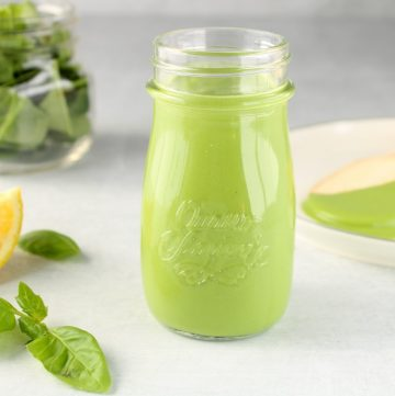 Showing in a small see through glass jar with a vegan creamy pesto sauce with more spinach leaves in the background as well as basil leaves and lemon wedges.