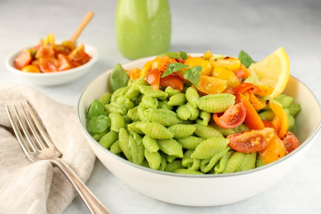 Close up on small noodles covered in a blended vegan creamy pesto sauce in a white bowl and topped with chopped cherry tomatoes.