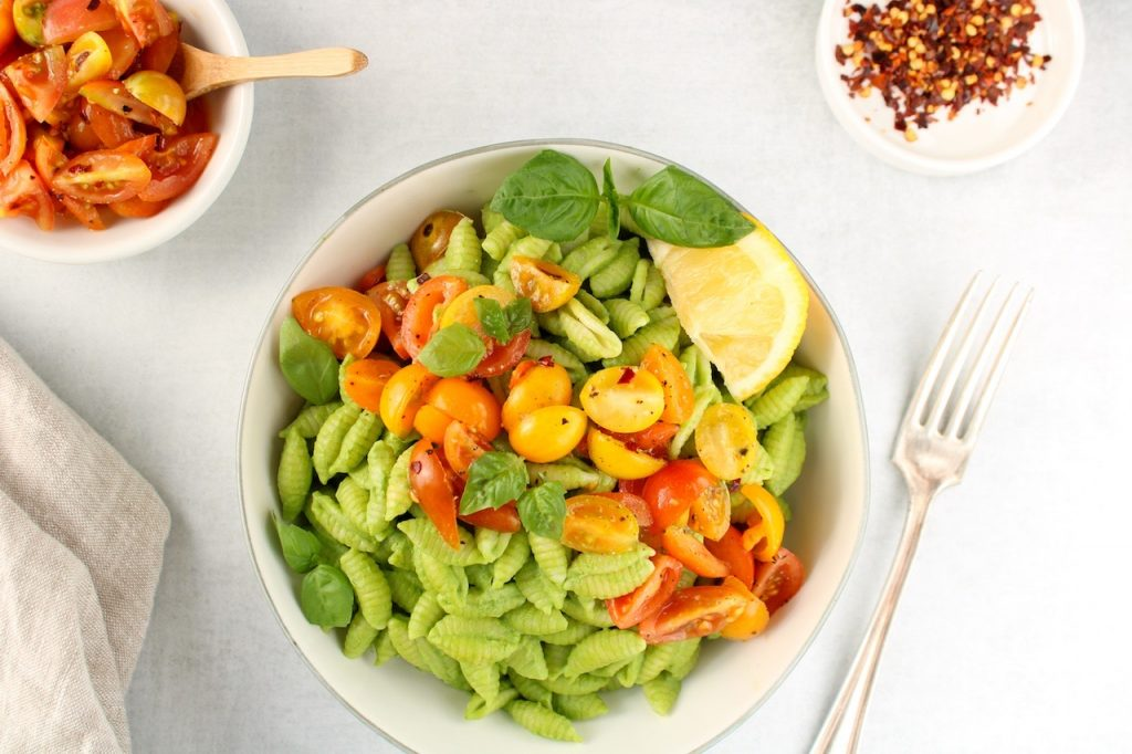 There is white bowl containing noodles covered in a vegan creamy pesto sauce and topped with sliced cherry tomatoes. Also in the bowl on the side, there is a slice of lemon and fresh basil leaves. On the table, there are 2 small bowls, one with red pepper flakes and the other with sliced tomatoes.