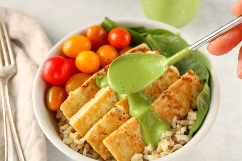 There is a spoon pouring a green sauce on roasted tofu that is laying on spinach, brown rice and cherry tomatoes.