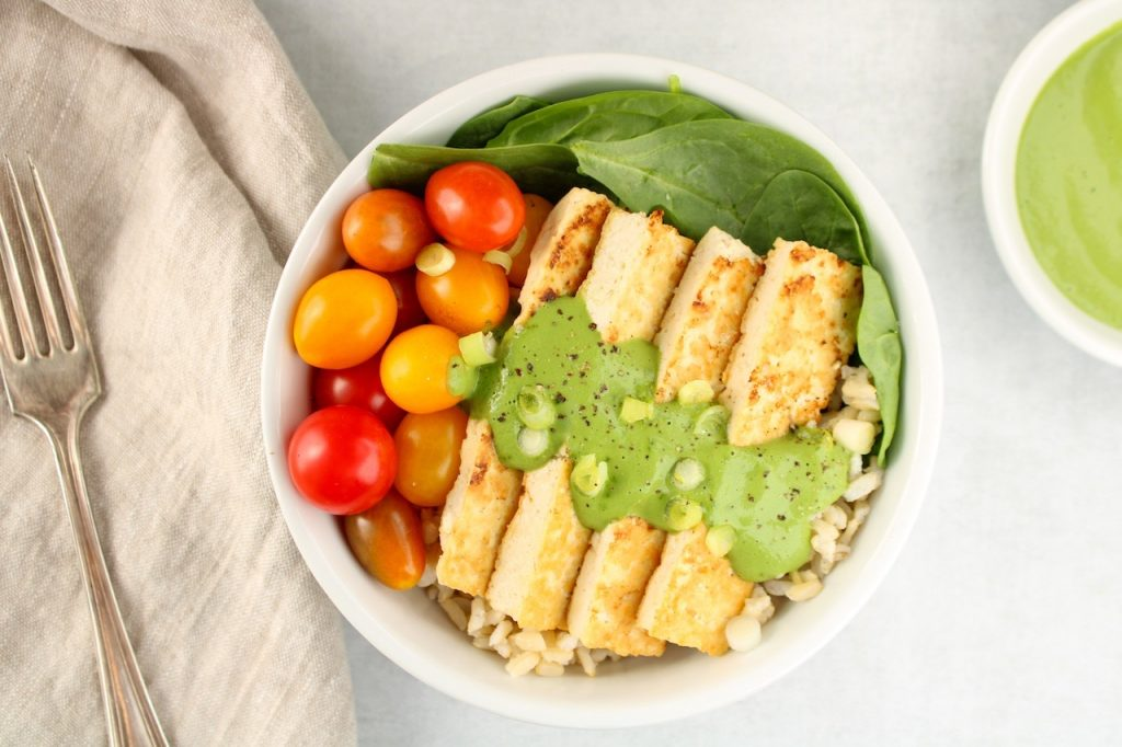 Displayed in a white bowl: fresh spinach, brown rice, roasted tofu and cherry tomatoes topped with a green sauce and green onion.