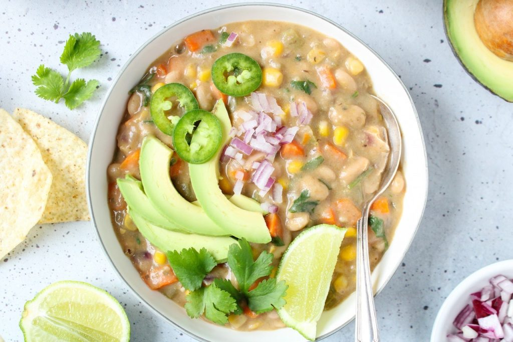 Close up on a white bowl containing a vegan white bean chili topped with diced red onion, sliced jalapeño and avocado, fresh cilantro and a lime wedge. Also on the table beside the bowl, there are a few tortilla chips, fresh cilantro, lime wedges and diced red onion in a small bowl.