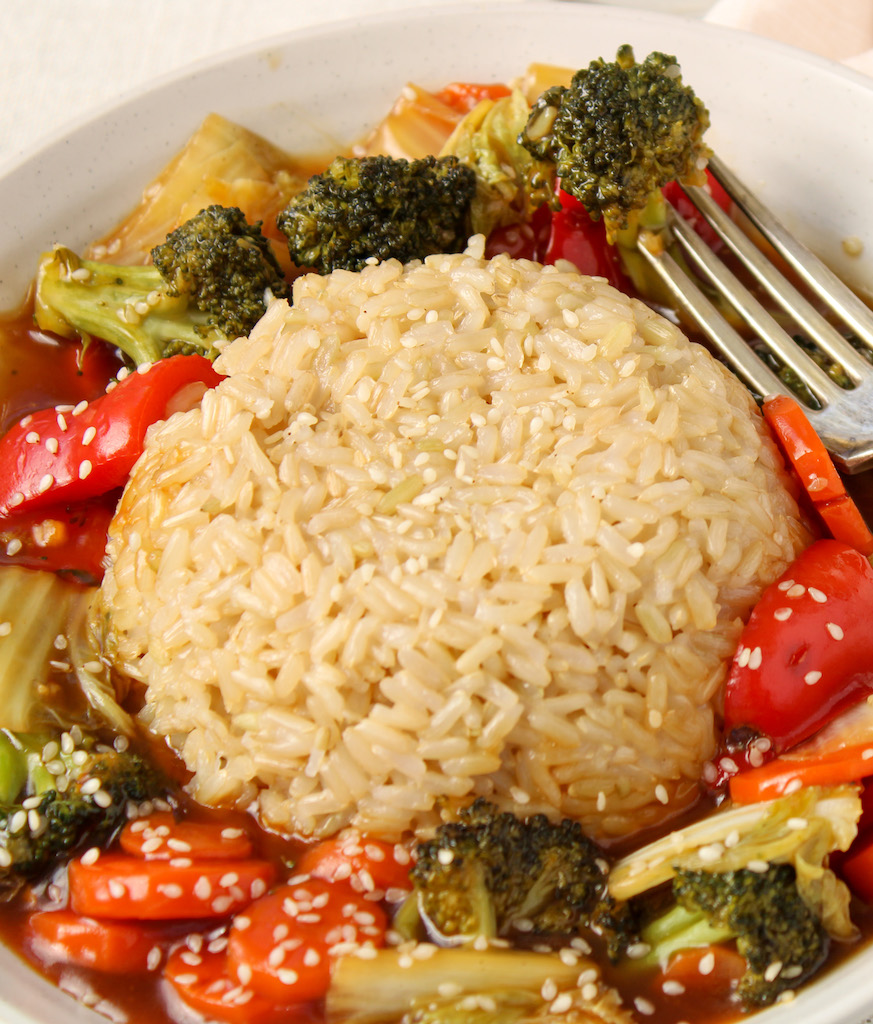 Close up on a bowl containing an healthy vegetable Stir-fry (with red pepper, carrots, broccoli and onions) that is topped with brown rice. Also, there is a fork on the side holding a piece of broccoli.