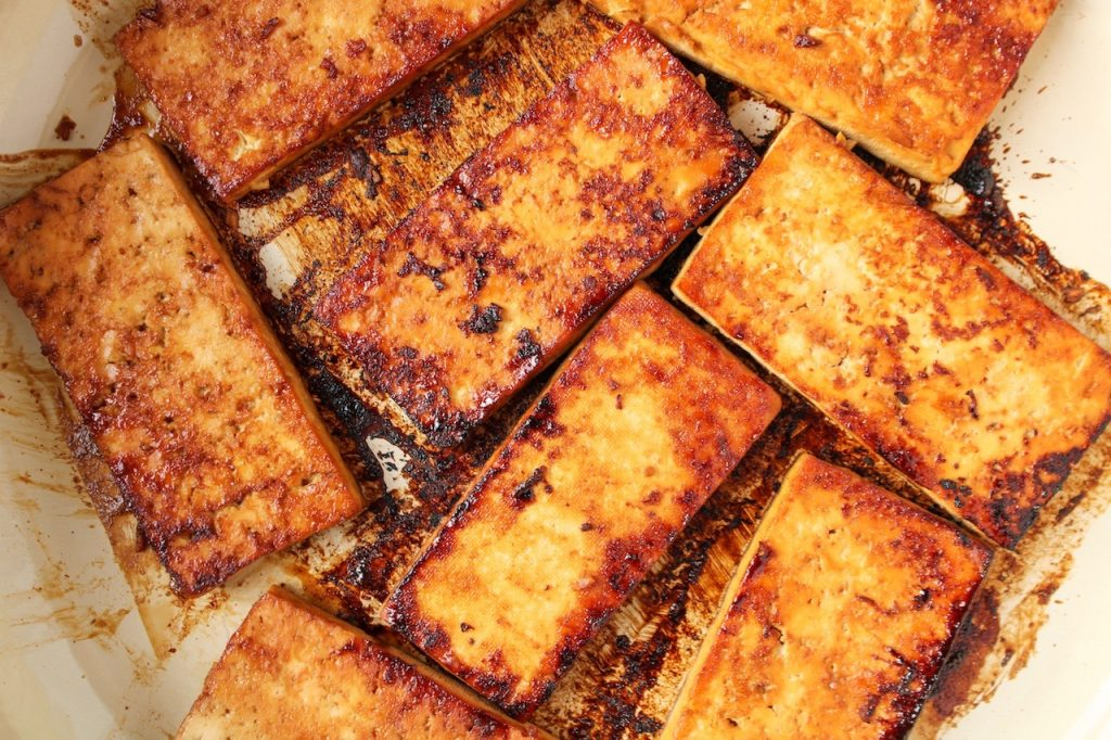 Close up on a few slices of tofu being cooked in a large pan. The tofu is brown since it was marinated first in a soy sauce mixture.