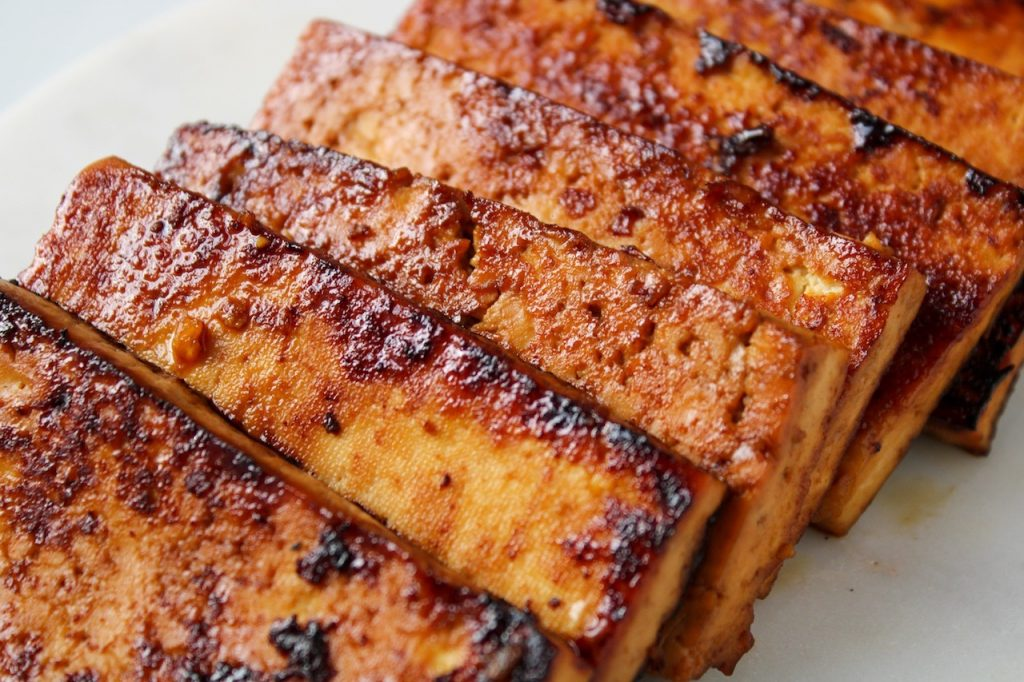 Close up on a few slices of tofu that have been marinated and pan roasted.