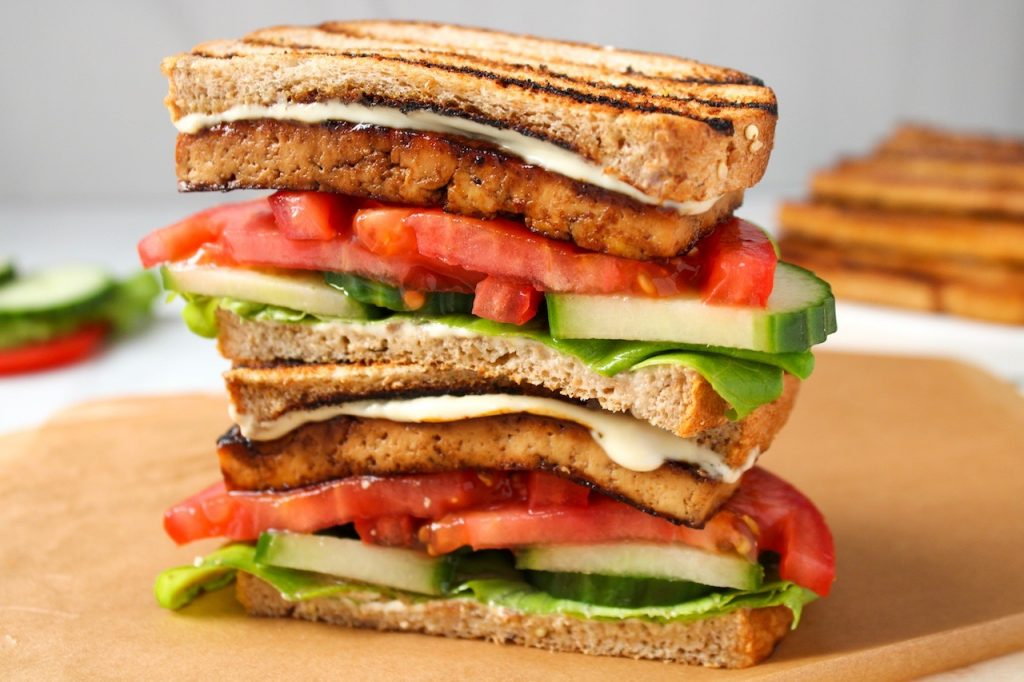 Close up on a marinated smoky tofu sandwich. The sandwich is cut in half and pilled on top of each other. In the sandwich, you can see the tofu, sliced tomatoes and cucumber, lettuce and a white sauce. In the background, you can see more smoky tofu, cucumber and lettuce.