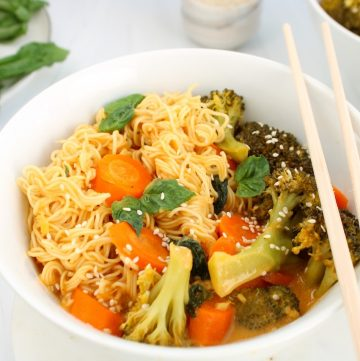 There is a one-pot broccoli ramen meal in a small white bowl with chop sticks on the side.