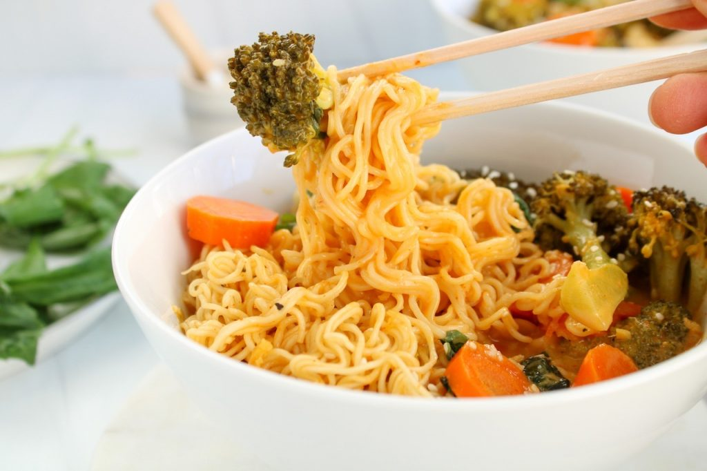 There is a one-pot broccoli ramen meal in a small white bowl with an hand holding on chop sticks that's grabbing on noodles from the bowl.